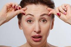 与皱痕的宏观妇女面孔在前额 胶原和面孔射入概念 更年期 库存图片