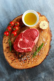 与盐、干胡椒、迷迭香、蕃茄和橄榄油的新鲜的未加工的牛排Ribeye, 图库摄影