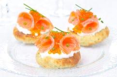 与盐味的三文鱼、红色鱼子酱和香葱的土豆小圆面包 免版税库存图片