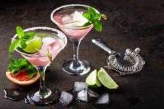 与盐味的外缘、新鲜的石灰和葡萄柚汁、冷的夏天柑橘刷新的饮料或者饮料的玛格丽塔鸡尾酒与冰 免版税库存图片
