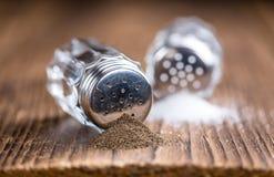与盐和胡椒罐的木桌 免版税库存照片