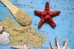 与盐的海星和海壳在蓝色背景 免版税图库摄影