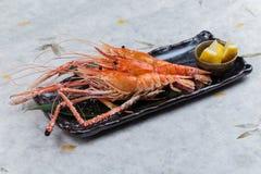 与盐的烤虾巨型老虎典当服务用在黑石板材的切的柠檬在washi日文报纸 库存照片