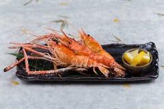 与盐的烤虾巨型老虎典当服务用在黑石板材的切的柠檬在washi日文报纸 库存图片