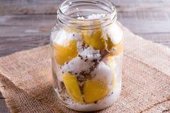 与盐的被保存的柠檬在瓶子的一个木板 免版税图库摄影