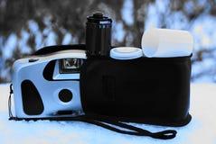 与盖子和一部影片的一台减速火箭的照相机在街道上的随风飘飞的雪 免版税库存图片