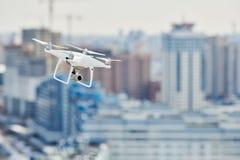 与盘旋在城市的数字照相机的寄生虫quadcopter 库存图片