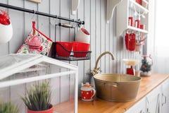 与盘的架子 内部浅灰色的厨房和红色圣诞节装饰 在家准备午餐在厨房概念 免版税库存图片