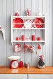 与盘的架子 内部浅灰色的厨房和红色圣诞节装饰 在家准备午餐在厨房概念 库存图片