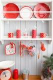 与盘的架子 内部浅灰色的厨房和红色圣诞节装饰 在家准备午餐在厨房概念 库存照片