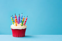 与盛开的蜡烛的生日杯形蛋糕 免版税库存图片