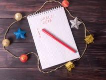 与目标的笔记薄和在新的Year& x27的一支红色铅笔; s背景 库存照片