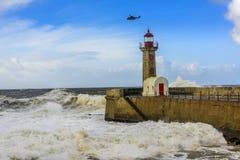 与直升机的巨大的波浪打击的灯塔在葡萄牙语大西洋 库存照片