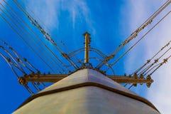 与相交高压电的导线的大电线杆 库存图片