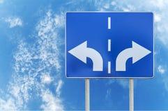 与相反箭头的路标在两标尺和天空背景 库存图片