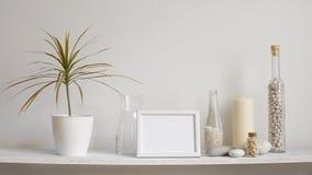 与相框大模型的现代室装饰 架子对有装饰蜡烛、玻璃和岩石的白色墙壁 投入d的手 影视素材