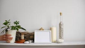 与相框大模型的现代室装饰 架子对有装饰蜡烛、玻璃和岩石的白色墙壁 投入d的手 股票视频