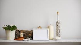 与相框大模型的现代室装饰 架子对有装饰蜡烛、玻璃和岩石的白色墙壁 投入d的手 股票录像