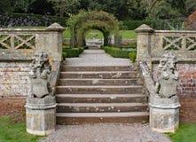 与盾的两个老石狮子雕象站立在一个小楼梯台阶的底部 免版税图库摄影