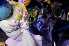 与看她的邪恶的巫婆的睡美人 金发的五颜六色的妇女有美丽的礼服的 有大微笑的恶魔显示牙 免版税库存图片