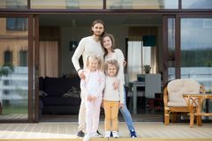 与看照相机的孩子的家庭站立在房子大阳台 库存图片