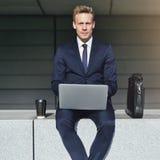 与看照相机的膝上型计算机的英俊的商人 库存照片