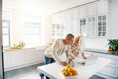 与看计算机的夫妇的厨房场面 免版税库存图片