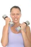与看起来沉默寡言的响铃的重量的健康少妇训练劳损 库存照片