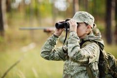 与看通过双筒望远镜的猎枪的猎人在森林里 图库摄影