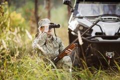 与看通过双筒望远镜的猎枪的猎人在森林里 免版税图库摄影