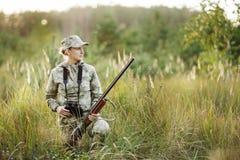 与看通过双筒望远镜的猎枪的猎人在森林里 库存照片