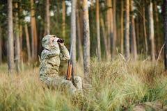 与看通过双筒望远镜的猎枪的猎人在森林里 免版税库存图片