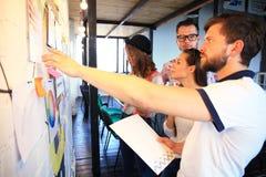 与看whiteboard的年轻伙伴的商人在创造性的办公室 库存照片