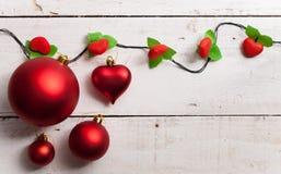 与真正的木绿色杉木,五颜六色的中看不中用的物品的圣诞快乐框架 免版税库存照片