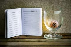 与眼睛球的笔记薄在木头和墙壁背景的玻璃 使用墙纸或背景万圣夜天图象的 库存图片