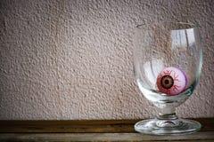 与眼睛球的笔记薄在木头和墙壁背景的玻璃 使用墙纸或背景万圣夜天图象的 免版税库存照片