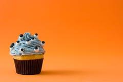 与眼睛的万圣夜杯形蛋糕在橙色背景 库存照片