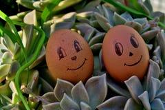 与眼睛的滑稽的在绿草的鸡蛋和微笑 免版税库存图片