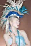 与眼睛的美丽的少妇佩带的羽毛头饰关闭了 免版税库存图片