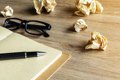 与眼睛玻璃和笔记本的被弄皱的纸球在木书桌上 库存图片
