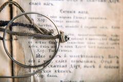 与眼镜的古老祈祷书在上面,在书的老斯拉夫的文本,顶视图,宏指令 免版税图库摄影