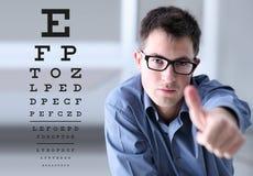 与眼镜的男性面孔在眼力测试图背景, sho 库存图片