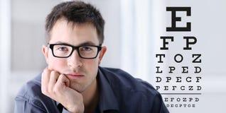 与眼镜的男性面孔在眼力测试图背景 库存照片