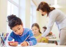 与着色铅笔的愉快的学校女孩图画 图库摄影