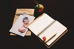 与睡觉的新出生的婴孩和空的笔记薄的卡片 库存图片