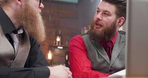 与短发的一个英俊的男性和与他的朋友的长的胡子在一次网上交谈时 股票录像