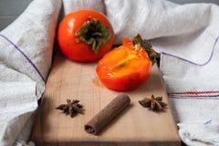 与石华和桂香的一个成熟柿子在木甲板 库存图片