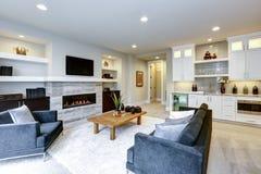 与石墙和firepl的美好的现代客厅内部 库存照片
