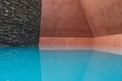 与石墙的蓝色室内游泳池 免版税库存照片