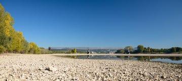 与石头的干燥河床,可看见的老铁路桥 库存照片